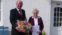 Bürgermeister Karl Hendlmeier überreicht der Jubilarin einen Geschenkkorb